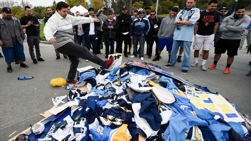 Chris Githens, left, kicks a pile of Chargers memorabilia in front of San Diego Chargers headquarters after the team announced that it will move to Los Angeles Thursday Jan. 12, 2017, in San Diego. (AP Photo/Denis Poroy)