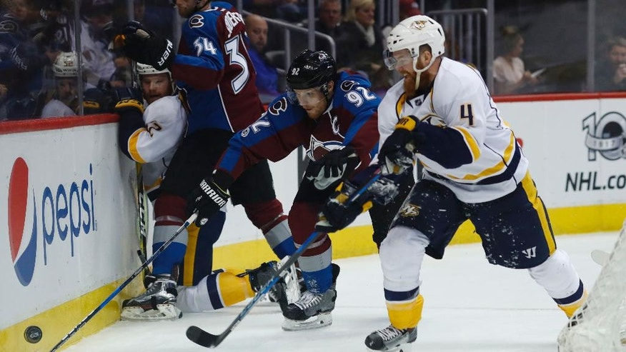 Colorado Avalanche left wing Gabriel Landeskog, left, of Sweden, fights for control of the puck with Nashville Predators defenseman Ryan Ellis in the first period of an NHL hockey game, Saturday, Jan. 14, 2017, in Denver. (AP Photo/David Zalubowski)