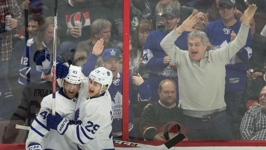 Fans react as Toronto Maple Leafs center Nazem Kadri, left, celebrates his second goal with teammate William Nylander during the third period of an NHL hockey game against the Ottawa Senators, Saturday, Jan. 14, 2017, in Ottawa, Ontario. (Adrian Wyld/The Canadian Press via AP)
