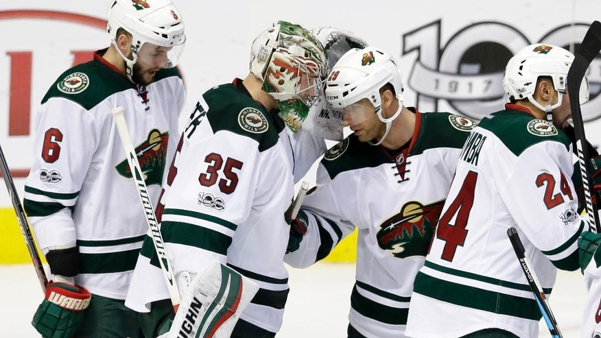 Minnesota Wild goalie Darcy Kuemper (35) is congratulated by Marco Scandella (6) and Jason Pominville (29) after their NHL hockey game against the Dallas Stars in Dallas, Saturday Jan. 14, 2017. (AP Photo/LM Otero)