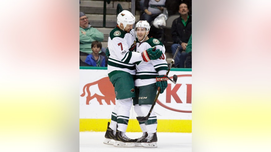 Minnesota Wild right wing Chris Stewart (7) and center Jordan Schroeder (10) celebrate a goal by Stewart in the first period of an NHL hockey game against the Dallas Stars in Dallas, Saturday Jan. 14, 2017. Schroeder had an assist on the score. (AP Photo/LM Otero)