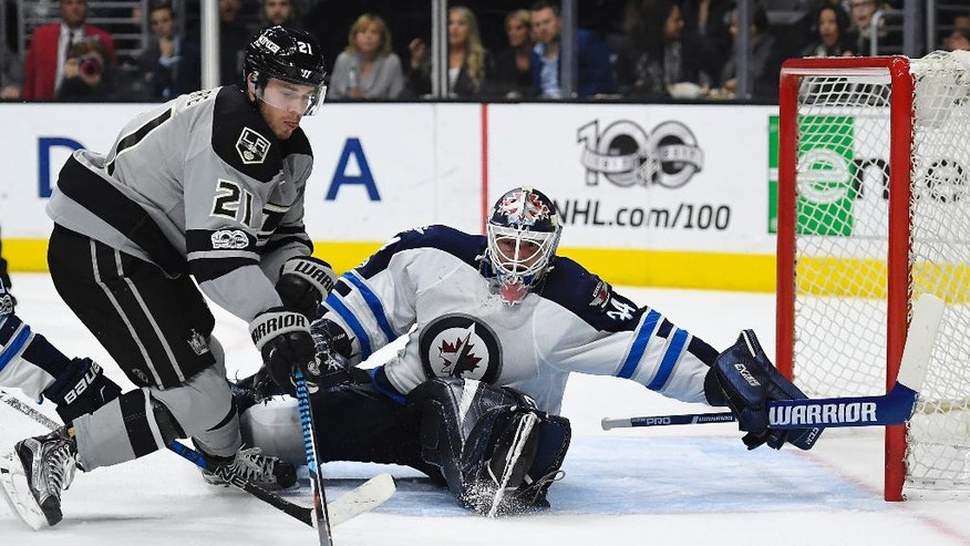 Los Angeles Kings center Nick Shore, left, tires to get a shot in on Winnipeg Jets goalie Michael Hutchinson during the second period of an NHL hockey game, Saturday, Jan. 14, 2017, in Los Angeles. (AP Photo/Mark J. Terrill)