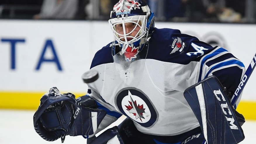 Winnipeg Jets goalie Michael Hutchinson watches a shot come toward him during the second period of an NHL hockey game against the Los Angeles Kings, Saturday, Jan. 14, 2017, in Los Angeles. (AP Photo/Mark J. Terrill)