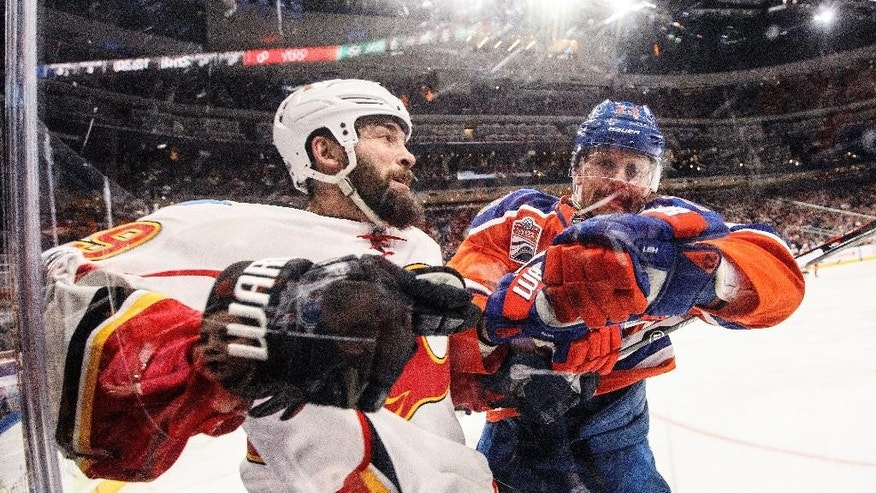 Calgary Flames' Deryk Engelland (29) is checked by Edmonton Oilers' Matt Hendricks (23) during the second period of an NHL hockey game Saturday, Jan. 14, 2017, in Edmonton, Alberta. (Jason Franson/The Canadian Press via AP)