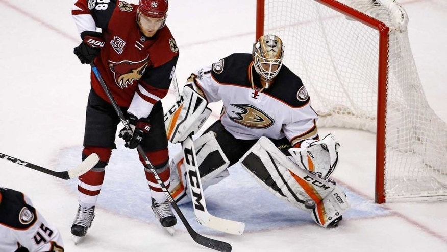 Anaheim Ducks goalie Jonathan Bernier (1) reaches out to make a save on a shot as Arizona Coyotes left wing Jamie McGinn (88) looks for a possible rebound during the third period of an NHL hockey game Saturday, Jan. 14, 2017, in Glendale, Ariz. The Ducks defeated the Coyotes 3-0. (AP Photo/Ross D. Franklin)