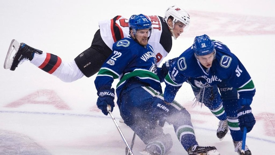 Vancouver Canucks left wing Daniel Sedin (22) and defenceman Troy Stecher (51) fight for control of the puck with New Jersey Devils right wing Beau Bennett (8) during the third period of an NHL hockey game in Vancouver, British Columbia, Sunday, Jan. 15, 2017. (Jonathan Hayward/The Canadian Press via AP)