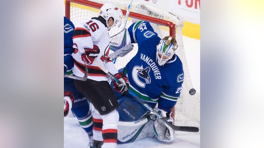New Jersey Devils center Jacob Josefson (16) tries to get a shot past Vancouver Canucks goalie Jacob Markstrom (25) during the third period of an NHL hockey game in Vancouver, British Columbia, Sunday, Jan. 15, 2017. (Jonathan Hayward/The Canadian Press via AP)