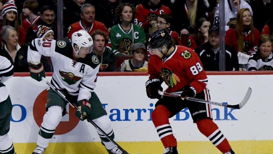 Minnesota Wild defenseman Ryan Suter (20) and Chicago Blackhawks right wing Patrick Kane (88) fight for the puck during the first period of an NHL hockey game on Sunday, Jan. 15, 2017, in Chicago. (AP Photo/Matt Marton)