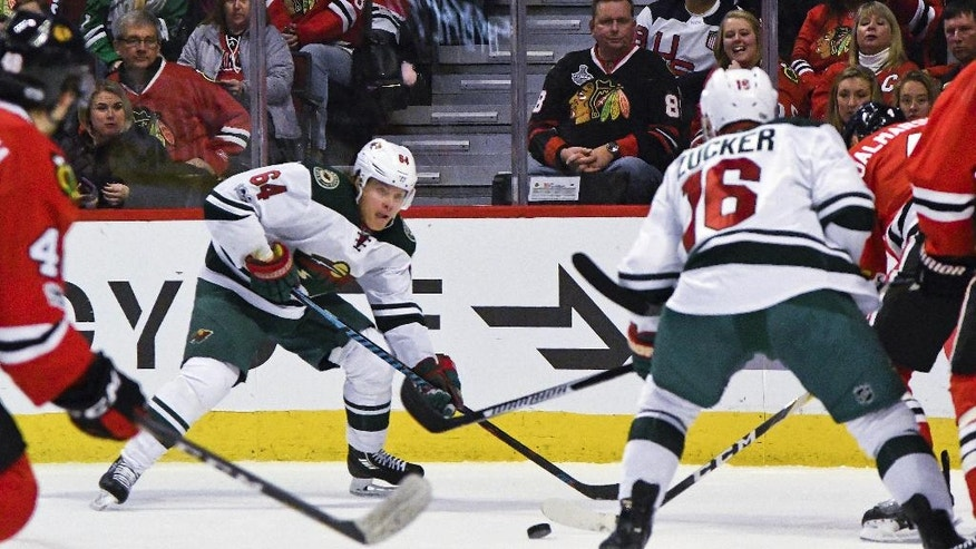 Minnesota Wild center Mikael Granlund (64) passes the puck against the Chicago Blackhawks during the first period of an NHL hockey game on Sunday, Jan. 15, 2017, in Chicago. (AP Photo/Matt Marton)