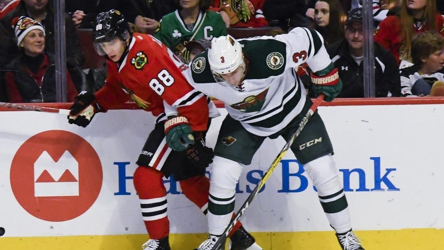 Chicago Blackhawks right wing Patrick Kane (88) and Minnesota Wild center Charlie Coyle (3) fight for the puck during the first period of an NHL hockey game on Sunday, Jan. 15, 2017, in Chicago. (AP Photo/Matt Marton)