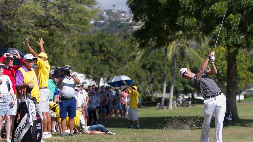 As the gallery watches, Justin Thomas hits off the rough on the third fairway during the final round of the Sony Open golf tournament, Sunday, Jan. 15, 2017, in Honolulu. (AP Photo/Marco Garcia)