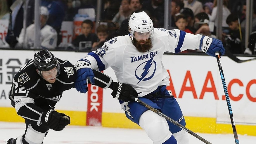 Los Angeles Kings center Trevor Lewis (22) reaches in to take away the puck from Tampa Bay Lightning defenseman Luke Witkowski (28) during the second period of an NHL hockey game in Los Angeles, Monday, Jan. 16, 2017. (AP Photo/Alex Gallardo)