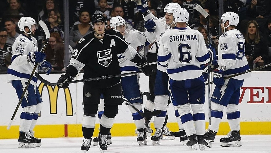 Los Angeles Kings right wing Dustin Brown (23) skates away as Tampa Bay Lightning center Brian Boyle, third from right, celebrates his goal with teammates during the second period of an NHL hockey game in Los Angeles, Monday, Jan. 16, 2017. (AP Photo/Alex Gallardo)
