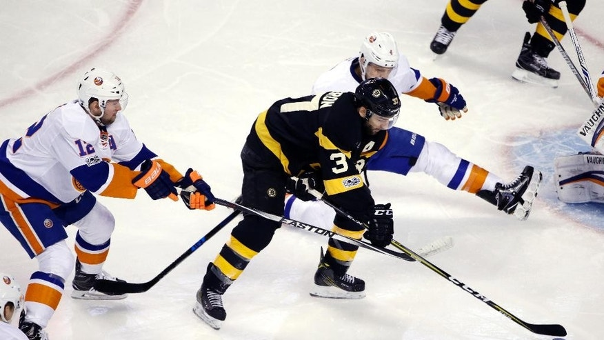 Boston Bruins center Patrice Bergeron (37) maneuvers the puck between New York Islanders left wing Josh Bailey (12) and defenseman Dennis Seidenberg (4) in the first period of an NHL hockey game, Monday, Jan. 16, 2017, in Boston. (AP Photo/Elise Amendola)