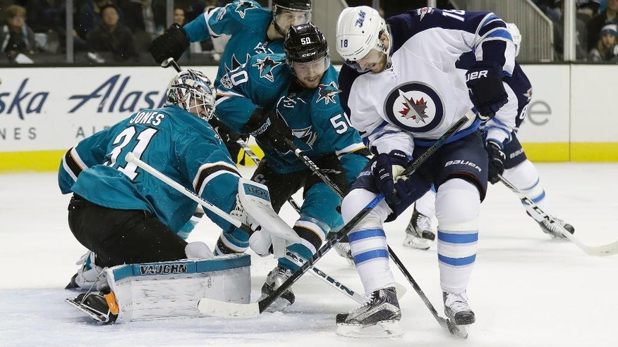 San Jose Sharks goalie Martin Jones, left, blocks a shot from Winnipeg Jets' Bryan Little (18) as the Sharks' Chris Tierney, center, closes in during the first period of an NHL hockey game, Monday, Jan. 16, 2017, in San Jose, Calif. (AP Photo/Marcio Jose Sanchez)