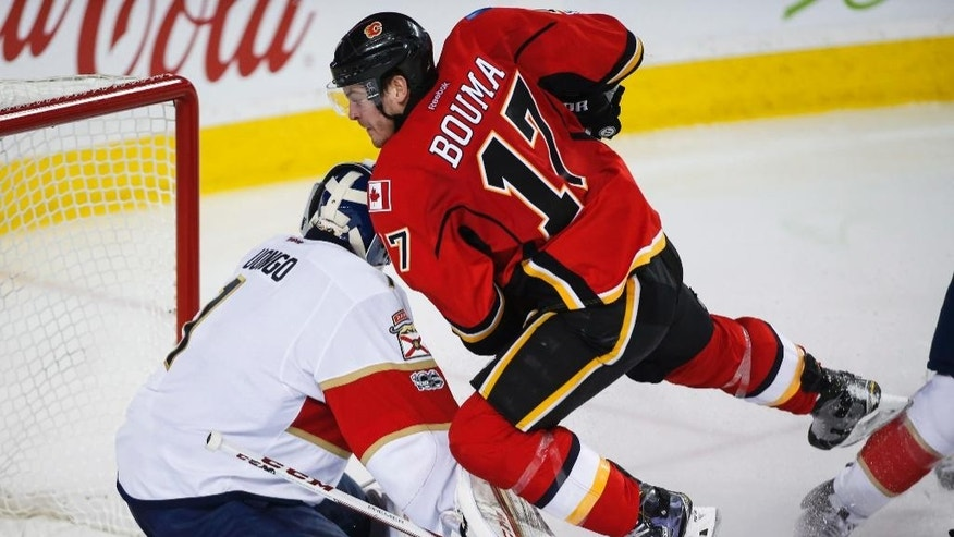 Florida Panthers goalie Roberto Luongo, left, ducks as Calgary Flames' Lance Bouma crashes over him during third period NHL hockey action in Calgary, Tuesday, Jan. 17, 2017. (Jeff McIntosh/The Canadian Press via AP)