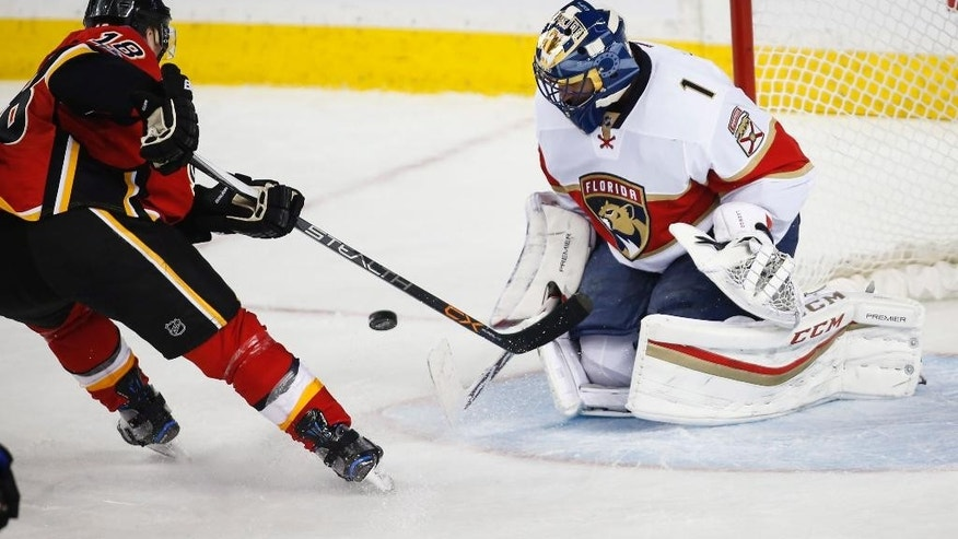Florida Panthers goalie Roberto Luongo, right, blocks a shot from Calgary Flames' Matt Stajan during second period NHL hockey action in Calgary, Tuesday, Jan. 17, 2017. (Jeff McIntosh/The Canadian Press via AP)
