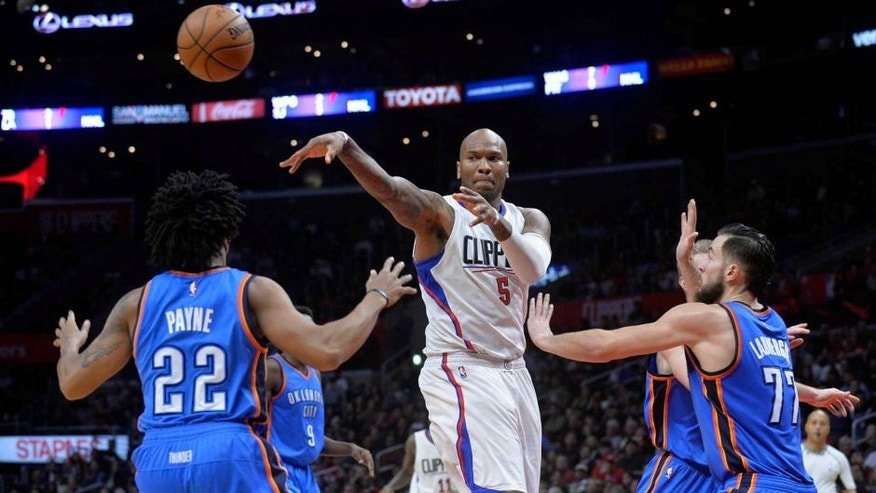 January 16, 2017; Los Angeles, CA, USA; Los Angeles Clippers center Marreese Speights (5) passes the ball against the defense of Oklahoma City Thunder guard Cameron Payne (22) and center Joffrey Lauvergne (77) during the second half at Staples Center. Mandatory Credit: Gary A. Vasquez-USA TODAY Sports