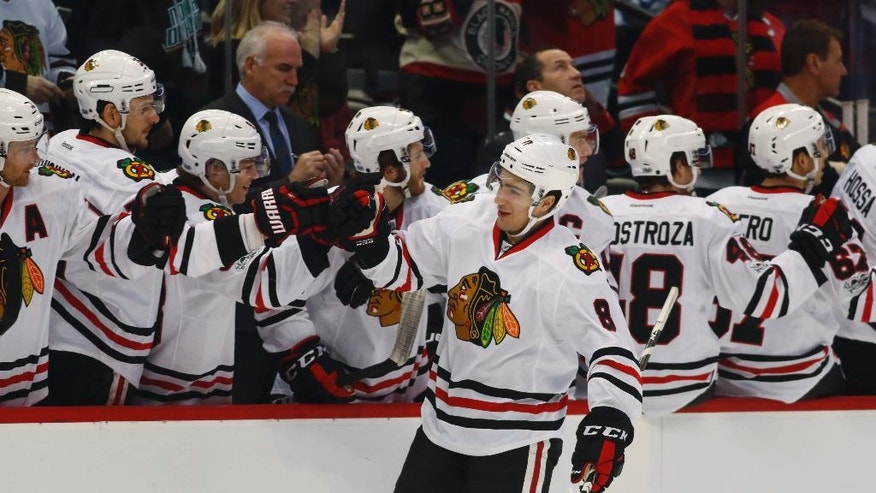 Chicago Blackhawks center Nick Schmaltz, front, is congratulated as he passes the team box after scoring a goal against the Colorado Avalanche in the first period of an NHL hockey game, Tuesday, Jan. 17, 2017, in Denver. (AP Photo/David Zalubowski)