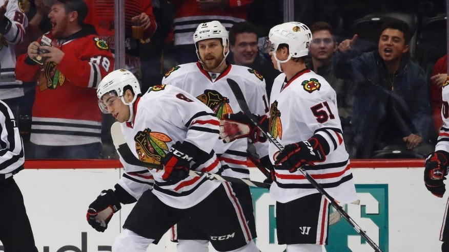 Chicago Blackhawks center Nick Schmaltz, left, is congratulated after scoring a goal by left wing Andrew Desjardins, center, and defenseman Brian Campbell against the Colorado Avalanche in the first period of an NHL hockey game, Tuesday, Jan. 17, 2017, in Denver. (AP Photo/David Zalubowski)