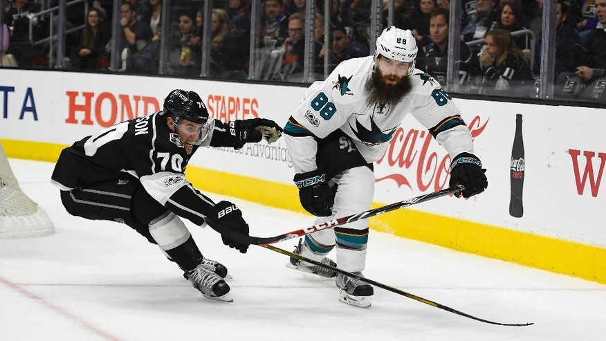 San Jose Sharks defenseman Brent Burns, right, passes the puck as Los Angeles Kings left wing Tanner Pearson reaches for the puck during the second period of an NHL hockey game, Wednesday, Jan. 18, 2017, in Los Angeles. (AP Photo/Mark J. Terrill)