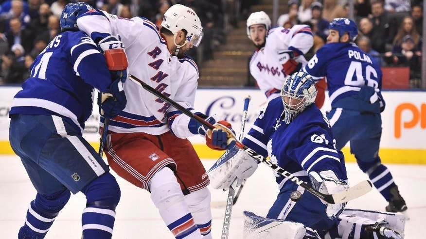 New York Rangers right wing Rick Nash (61) shoots on Toronto Maple Leafs goalie Frederik Andersen (31) as Maple Leafs center Auston Matthews (34) defends during the first period of an NHL hockey game, Thursday, Jan. 19, 2017 in Toronto. (Frank Gunn/The Canadian Press via AP)