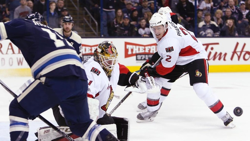 Ottawa Senators' Mike Condon, center, makes a save against the Columbus Blue Jackets as teammate Dion Phaneuf watches the puck during the second period of an NHL hockey game Thursday, Jan. 19, 2017, in Columbus, Ohio. (AP Photo/Jay LaPrete)