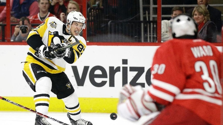 Pittsburgh Penguins' Sidney Crosby (87) makes a shot on goal against Carolina Hurricanes goalie Cam Ward (30) during the first period of an NHL hockey game in Raleigh, N.C., Friday, Jan. 20, 2017. (AP Photo/Gerry Broome)