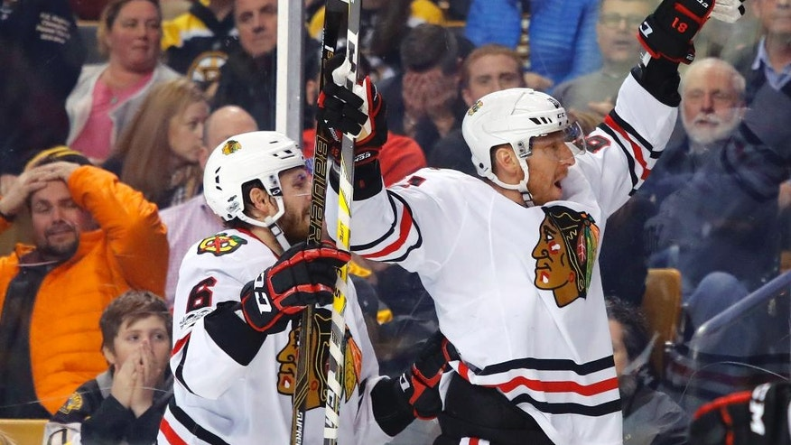 As Boston Bruins fans watch, Chicago Blackhawks' Marian Hossa celebrates his goal with Michal Kempny (6) during the third period of the Chicago Blackhawks' 1-0 win over the Bruins in an NHL hockey game in Boston on Friday, Jan. 20, 2017. (AP Photo/Winslow Townson)