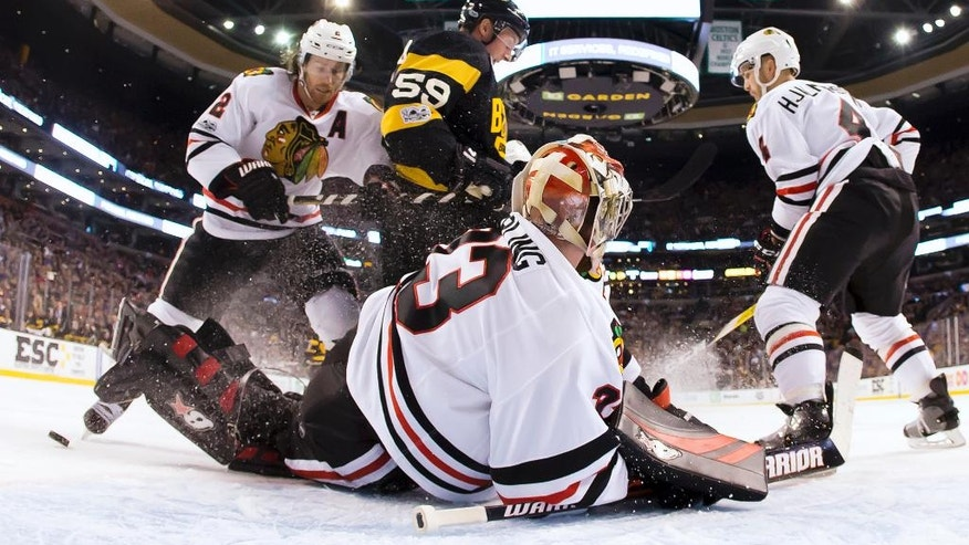 Chicago Blackhawks defenseman Duncan Keith (2) and Boston Bruins center Tim Schaller look for a rebound after a save by Blackhawks goalie Scott Darling during the second period of the Blackhawks' 1-0 win in an NHL hockey game in Boston Friday, Jan. 20, 2017. (AP Photo/Winslow Townson)