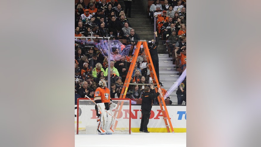 Anaheim Ducks goalie John Gibson watches as workers remove a cracked plexiglass piece during the second period of an NHL hockey game against the Colorado Avalanche Thursday, Jan. 19, 2017, in Anaheim, Calif. (AP Photo/Jae C. Hong)