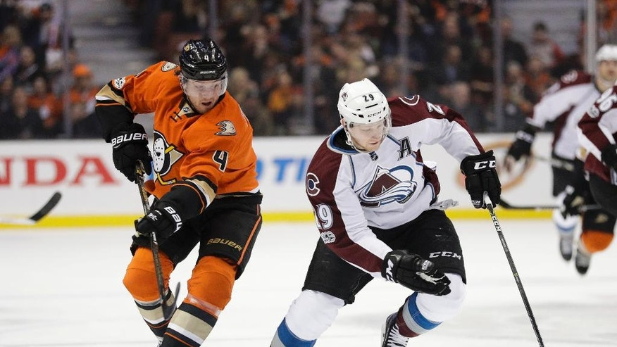 Colorado Avalanche's Nathan MacKinnon, right, moves the puck past Anaheim Ducks' Cam Fowler during the first period of an NHL hockey game Thursday, Jan. 19, 2017, in Anaheim, Calif. (AP Photo/Jae C. Hong)