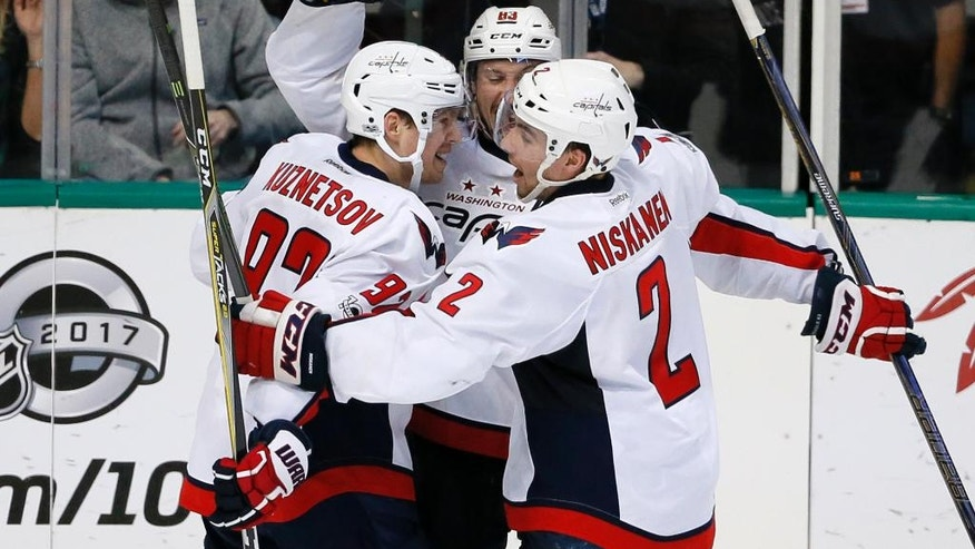 Washington Capitals' Evgeny Kuznetsov (92), Matt Niskanen (2) and Jay Beagle, rear, celebrate Beagle's overtime goal against the Dallas Stars in the Capitals' 4-3 win in an NHL hockey game, Saturday, Jan. 21, 2017, in Dallas. (AP Photo/Tony Gutierrez)