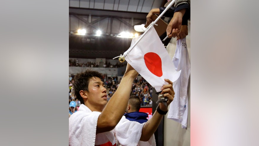 Japan's Kei Nishikori signs autographs as he leaves Margaret Court Arena following his win over Slovakia's Lukas Lacko in their third round match at the Australian Open tennis championships in Melbourne, Australia, Friday, Jan. 20, 2017. (AP Photo/Aaron Favila)