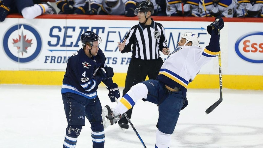 St. Louis Blues' Ryan Reaves (75) is checked by Winnipeg Jets' Paul Postma (4) during first period of an NHL hockey game in Winnipeg, Manitoba, Saturday, Jan. 21, 2017. (John Woods/The Canadian Press via AP)