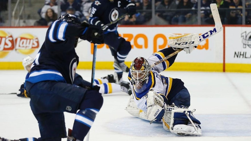 St. Louis Blues goaltender Pheonix Copley (30) saves a shot from Winnipeg Jets' Mathieu Perreault (85) as Jets' Blake Wheeler (26) looks on during the second period of an NHL hockey game in Winnipeg, Manitoba, Saturday, Jan. 21, 2017. (John Woods/The Canadian Press via AP)
