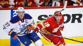 Edmonton Oilers' Connor McDavid, left, tangles with Calgary Flames' Matt Stajan during the second period of an NHL hockey game Saturday, Jan. 21, 2017, in Calgary, Alberta. (Jeff McIntosh/The Canadian Press via AP)