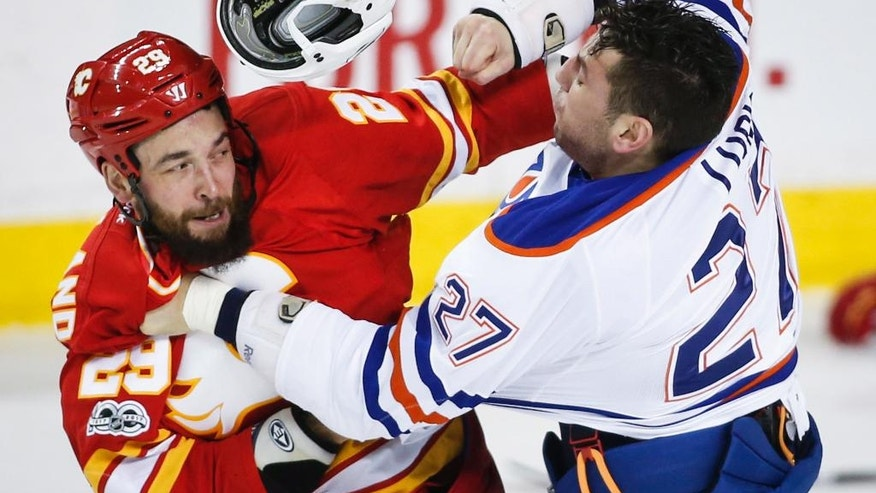 Edmonton Oilers' Milan Lucic (27) tussles with Calgary Flames' Deryk Engelland during the first period of an NHL hockey game Saturday, Jan. 21, 2017, in Calgary, Alberta. (Jeff McIntosh/The Canadian Press via AP)
