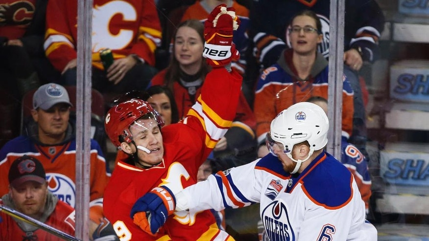 Edmonton Oilers' Adam Larsson, right, of Sweden, checks Calgary Flames' Matthew Tkachuk during the first period of an NHL hockey game in Calgary, Saturday, Jan. 21, 2017. (Jeff McIntosh/The Canadian Press via AP)