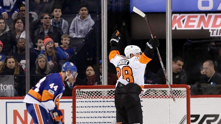Philadelphia Flyers' Claude Giroux, top, reacts after scoring the winning goal past New York Islanders goalie Thomas Greiss during overtime of the NHL hockey game, Sunday, Jan. 22, 2017, in New York. The Flyers defeated the Islanders in overtime 3-2. (AP Photo/Seth Wenig)
