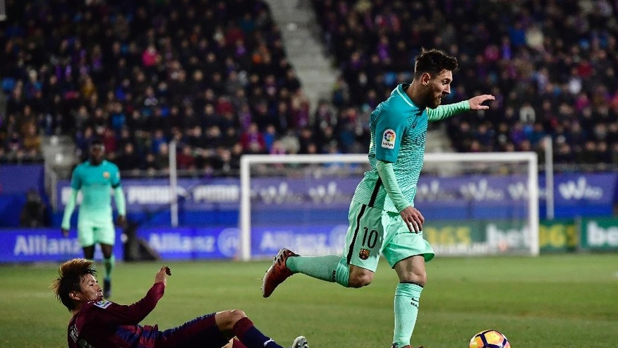 FC Barcelona's Lionel Messi, right, in action with Eibar's Takashi Inui, during the Spanish La Liga soccer match between FC Barcelona and Eibar, at Ipurua stadium in Eibar, northern Spain, Sunday, Jan. 22, 2017. (AP Photo/Alvaro Barrientos)