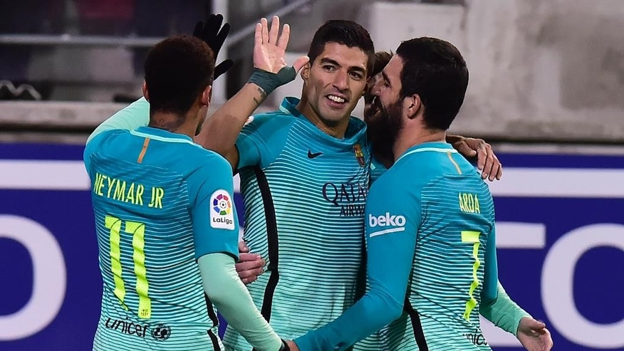 FC Barcelona's Luis Suarez, center celebrates with Neymar Jr. and Arda Turan, right, after scoring against Eibar during the Spanish La Liga soccer match between FC Barcelona and Eibar, at Ipurua stadium in Eibar, northern Spain, Sunday, Jan. 22, 2017. (AP Photo/Alvaro Barrientos)
