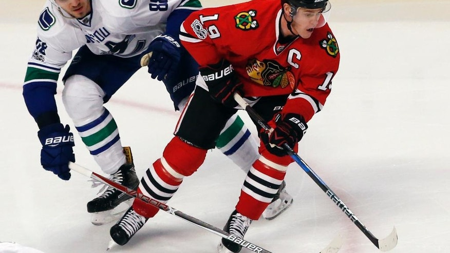 Chicago Blackhawks center Jonathan Toews, right, controls the puck against Vancouver Canucks defenseman Nikita Tryamkin during the third period of an NHL hockey game Sunday, Jan. 22, 2017, in Chicago. The Blackhawks won 4-2. (AP Photo/Nam Y. Huh)