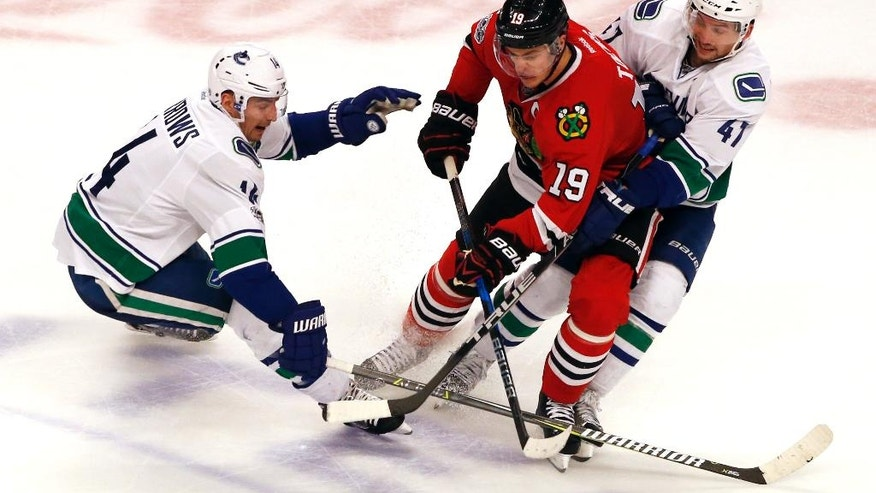 Chicago Blackhawks center Jonathan Toews, center, battles for the puck between Vancouver Canucks right wing Alexandre Burrows, left, and left wing Sven Baertschi during the third period of an NHL hockey game Sunday, Jan. 22, 2017, in Chicago. The Blackhawks won 4-2. (AP Photo/Nam Y. Huh)