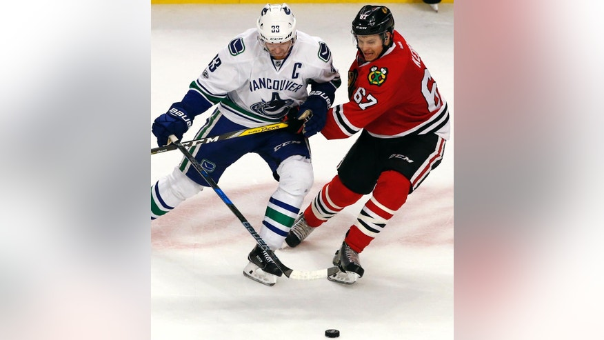 Vancouver Canucks center Henrik Sedin, left, battles for the puck against Chicago Blackhawks center Tanner Kero during the third period of an NHL hockey game Sunday, Jan. 22, 2017, in Chicago. The Blackhawks won 4-2. (AP Photo/Nam Y. Huh)