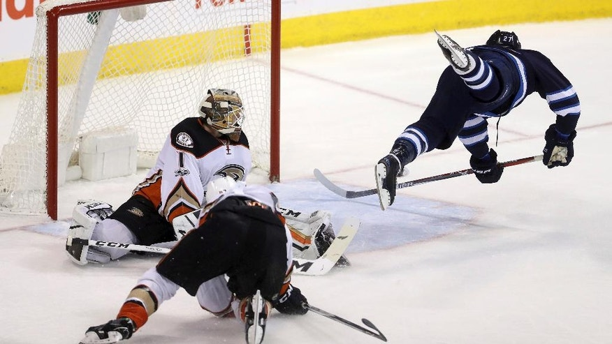 Winnipeg Jets' Nikolaj Ehlers (27) soars through the air as he scores on Anaheim Ducks goaltender Jonathan Bernier (1) with Ducks' Hampus Lindholm (47) trailing behind during third period NHL hockey action in Winnipeg, Monday, Jan. 23, 2017. (Trevor Hagan/The Canadian Press via AP)