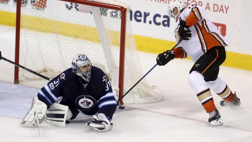 Winnipeg Jets goaltender Ondrej Pavelec (31) makes a save on Anaheim Ducks' Corey Perry (10) during third period NHL hockey action in Winnipeg, Monday, Jan. 23, 2017. (Trevor Hagan/The Canadian Press via AP)