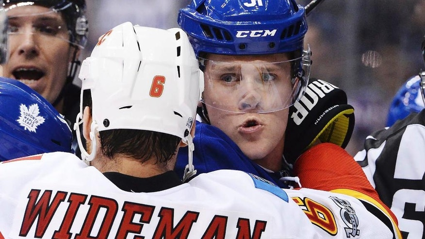 Calgary Flames defenseman Dennis Wideman (6) grabs Toronto Maple Leafs defenseman Jake Gardiner (51) during third period NHL hockey action in Toronto on Monday, Jan. 23, 2017. (Nathan Denette/The Canadian Press via AP)