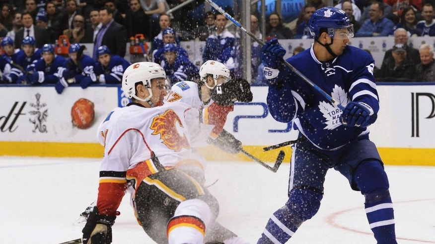 Calgary Flames center Mikael Backlund (11) is hit by Toronto Maple Leafs defenseman Connor Carrick (8) during the third period of an NHL hockey game in Toronto on Monday, Jan. 23, 2017. (Nathan Denette/The Canadian Press via AP)