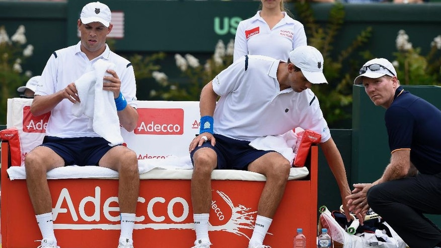 FILE - In this March 5, 2016 file photo, Jim Courier, right, captain of the United States Davis Cup team, talks to doubles players Bob, left, and Mike Bryan while playing against Australia's Lleyton Hewitt and John Peers during their Davis Cup doubles match in Melbourne, Australia. Bob and Mike Bryan announced Sunday, January, 22, 2017, that they are retiring from playing Davis Cup for the United States after 14 years with the team. (AP Photo/Andrew Brownbill,File)